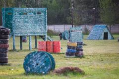 Boy is playing paintball on the field. two teams of paintball players in camouflage form with masks, helmets, guns on the field royalty free stock photos