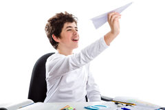 Boy playing with a paper airplane in front of homework blank boo Stock Image
