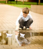Boy is playing with paper boat Royalty Free Stock Photography