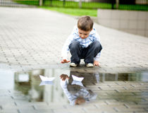 Boy is playing with paper boat Stock Photography