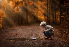 Boy playing with the paper boat. Little boy playing with the paper boat in the autumn forest puddle Royalty Free Stock Image