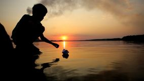 Boy Playing With Paper Boat. Little boy playing with paper boat on water stock video footage