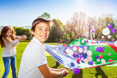 Boy playing parachute with friends in summer park Stock Image