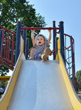Boy playing in park. Young boy playing on a slide at the park Stock Photo