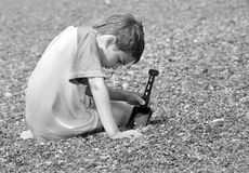 Boy playing in pebble Stock Images