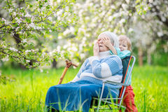 Boy playing peekaboo with his great grandmother Royalty Free Stock Images
