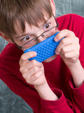 Boy playing with phone. A middle school teenage boy using his cell phone or portable music MP3 player at school Stock Photos