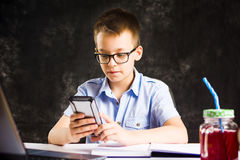 Boy playing the phone while doing homework. At home Royalty Free Stock Photography