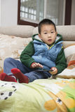 Boy playing phone. One boy playing game on phone sitting on sofa  at home Royalty Free Stock Photos