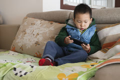 Boy playing phone Stock Image
