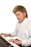 Boy playing piano. Blonde boy playing piano; isolated on white backgound Stock Images
