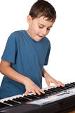 Boy playing piano. Cute kid playing piano, isolated on white background Stock Photo
