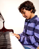Boy playing piano Stock Images