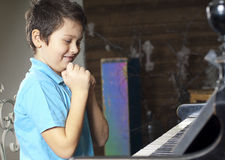 Boy is playing the piano royalty free stock photography