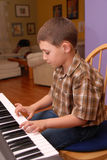 Boy playing piano. Young boy playing piano or keyboard,6-7 year old Stock Image