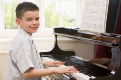 Boy Playing Piano. And smiling Stock Photos