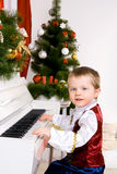 Boy playing the piano on eve of Christmas. Beautiful boy playing the piano on eve of Christmas Royalty Free Stock Images