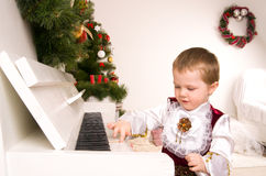 Boy playing the piano on eve of Christmas Stock Photos