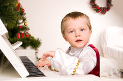 Boy playing the piano on eve of Christmas. Beautiful boy playing the piano on eve of Christmas Royalty Free Stock Photos