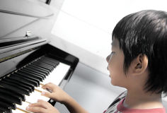 Boy playing piano. A young asian boy is playing the piano Royalty Free Stock Photo