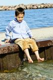Boy playing on pier. Portrait of young boy dipping feet in lake from pier royalty free stock photos