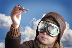 Boy playing with pilots hat and airport background