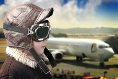 Boy playing with pilots hat and airport background Stock Photography