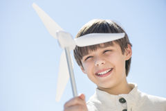 Boy Playing With Pinwheel Against Clear Blue Sky Stock Photos