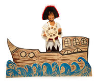 Boy playing pirate no cardboard ship steering. Boy playing in home theater wearing pirate costume and sailing on cardboard ship steering helm looking at camera Stock Image