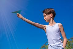 Boy playing plane of paper stock photography
