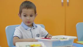 Boy playing with plastic building blocks at kindergarten stock video