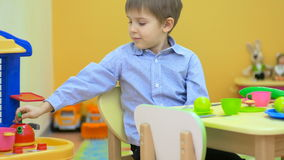 The boy playing with plastic dishes in children`s room stock video