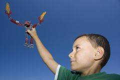 Boy playing with plastic robot. Cute kid playing with a robot toy Royalty Free Stock Images