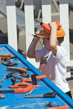 Boy playing with plastic tools. He's wearing a helmet and has lots of tools in front of him Royalty Free Stock Photo