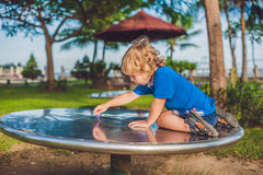 Boy playing on the playground in the background of green grass Royalty Free Stock Photo