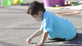 Boy Playing In Playground With Chalk stock video footage