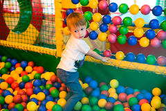 Boy playing on the playground. In the children's maze with balls. Multi-colored balls, soft walls and floor for children Stock Image
