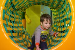 Boy playing on the playground, in the children`s maze. Little kid playing in children room royalty free stock images
