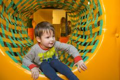 Boy playing on the playground, in the children`s maze. Little kid playing in children room stock photography