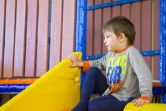 Boy playing on the playground, in the children`s maze. children`s slide.  stock photos