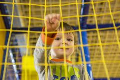 Boy playing on the playground, in the children`s maze. Ttle kid playing in children room royalty free stock photo