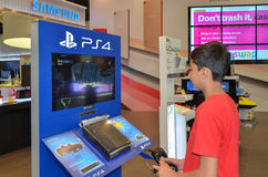 Boy Playing Playstation 4 in Sony Center, Dubai Mall, Dubai. Sony Center Dubai Mall, United Arab Emirates Stock Photo
