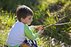 Boy playing by a pond on a sunny day Stock Image
