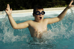 Boy playing in pool. Boy playing in the pool and has a lot of fun in summertime royalty free stock photo