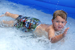 Boy playing in pool. Cute young boy playing in paddling pool Royalty Free Stock Images