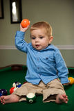 Boy playing on pool table. Preschool boy playing with billiard balls on pool table Stock Photo