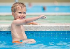 Boy playing in a pool of water Royalty Free Stock Images