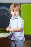 Boy playing in preschool class. Little boy playing in preschool class with building blocks royalty free stock photos