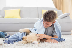 Boy playing with puppy lying on rug Royalty Free Stock Photography