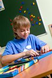 Boy playing with puzzles stock images